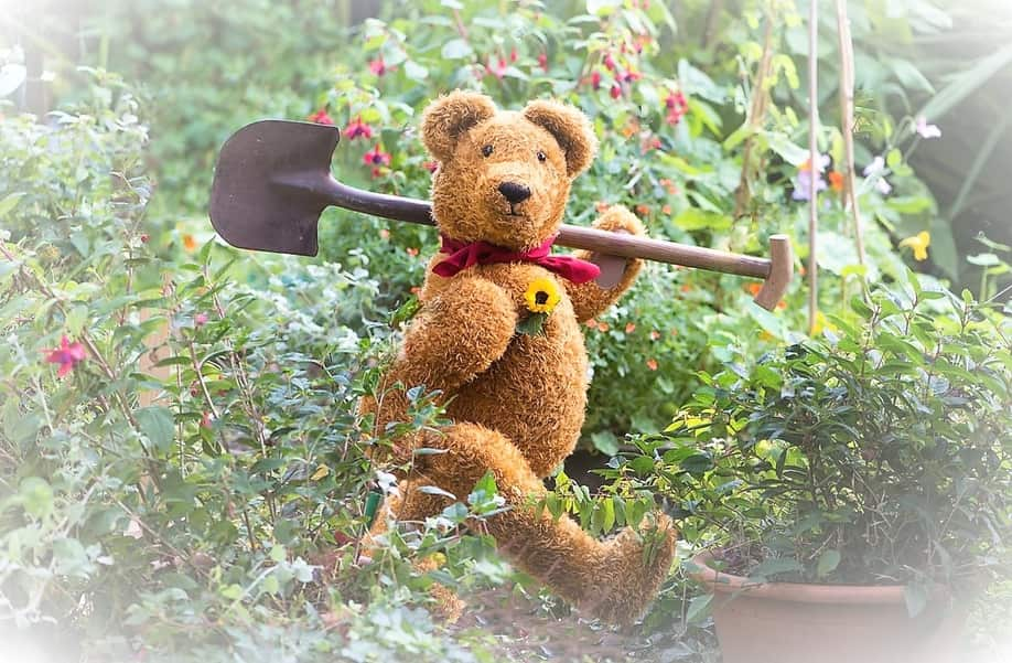 Gardener Landscaper bear with spade walking through garden